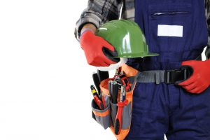 Young electrician technician wearing protective gloves and helmet in the hands isolated on white background.